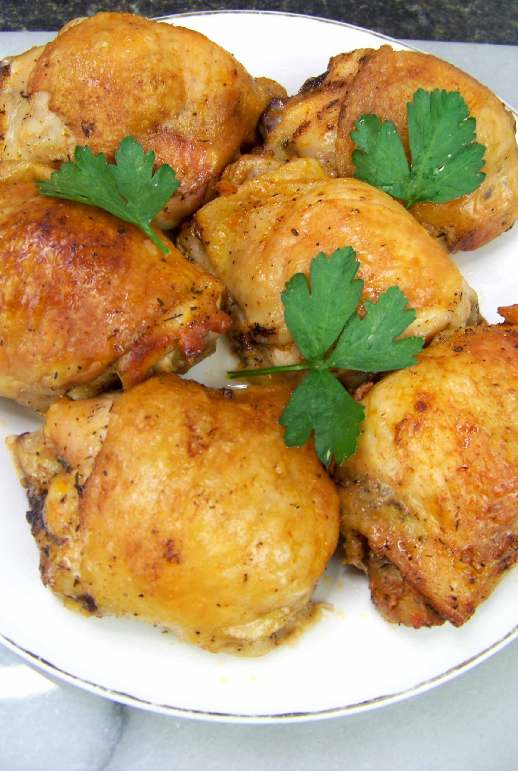 baked chicken thighs on a white plate and garnished with fresh parsley